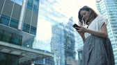 contemporâneo : Woman uses a smartphone on the background of business centers on the street