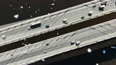 construcción de carreteras : Aerial view of trucks and cars driving on a cable-stayed bridge over the river