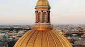 Flying on a drone around the dome of St. Isaacs Cathedral in St. Petersburg at sunset, close-up
