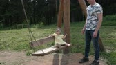 happy father in t-shirt and jeans swings little daughter