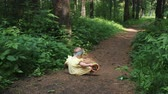 funny girl with orange bucket sits on brown forest path