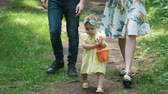 toddler girl in dress holds bucket walking by mother father Stok Video