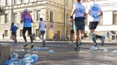maraton : People run a marathon and throw plastic water bottles on the asphalt in slow motion