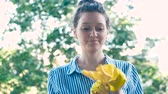 lavavetri : pretty lady in blue white shirt puts on yellow rubber gloves Filmati Stock