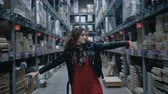 koper : pretty girl dancing a wave with a phone in a large industrial stock room