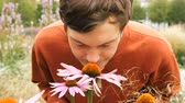 花序 : handsome man with brown hair sniffs beautiful echinacea