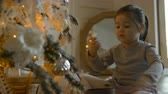 paardenstaart : interested toddler girl looks at Christmas tree decorations