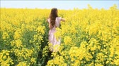 kwiaty : Female Model in Vintage Dress Walking through Yellow Field Touching Grass HD