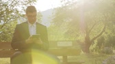 reading : Happy Working Man In Suit in Nature Park Sun Flare HD