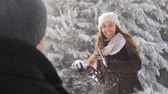 obrana : Winter Playful Woman Throwing Snow Balls at Man Joy Christmas