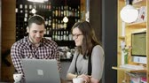 Young Man And Woman Drinking Coffee And Working On A Laptop At The Coffee Bar Smiling Discussing Project Online Business Concept Slow Motion Shot