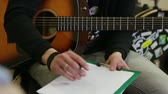 guitarrista : Guy with an acoustic guitar writes chords on a sheet. Vídeos