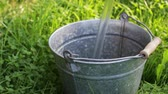 regenwasser : Bottomless metal bucket is endless filled with water in the grass, video looped