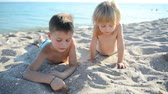 playful : Children on a beach draw on sand