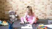 Little beautiful girl draws sitting on the floor and plays with toys. Stabilized shot. 4K video.