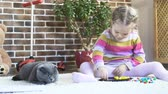 Little beautiful girl draws and sitting on the floor with his cat. Stabilized and very smooth shot. 4K video.