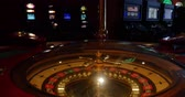 povznášející : A 4k wide shot of a casino roulette in the foreground and some slot machines in the background...