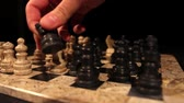 knocking : A black knight eats a white pawn in a chess game, isolated on black background... Stock Footage