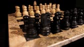 lined up : Side shot of a chess board with its figures lined up, the focus goes from black to white figures...