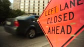 tabela : Left lane closed construction warning sign with street in background.