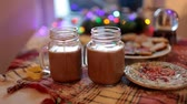 advento : Two mugs with cocoa and marshmallows are on the Christmas table. Stock Footage