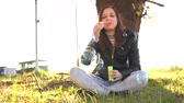 sabun : Young beautiful woman blowing soap bubbles. Girl and soap bubbles in park Stok Video