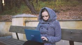 escritor : A woman wearing a sweater jacket Girl writing on laptop on park bench