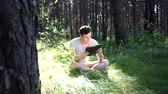 literatura : Man reading a book in a green summer forest.