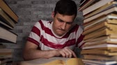 tankönyv : Man student boring reading book at library with a lot of books in university. Student disheartened reading book for examination.