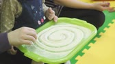 sêmola : Child draws a finger in the tray with a semolina