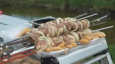 broiling : Man putting skewers with fresh meat on the table