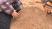 coat : Children playing with sand and learning how to make shapes in outdoor sandbox. Close-up