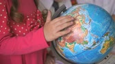movimentar se : Preschool girl rotates the model of globe of world at the lesson. Close-up Vídeos