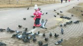 scaring : VELIKIY NOVGOROD, RUSSIA - MART 25, 2017: Children running after pigeons in the park in spring