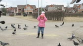 scaring : VELIKIY NOVGOROD, RUSSIA - MART 22, 2017: Little child scares pigeons in the park in spring