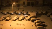 VELIKIY NOVGOROD, RUSSIA - JANUARY 14, 2017: View from above night - courtyard of residential city house during snowfall - cars covered with snow. Ambulance in yard waiting doctors and sick patient