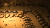 VELIKIY NOVGOROD, RUSSIA - JANUARY 14, 2017: View from above night - courtyard of residential city house during snowfall - cars covered with snow. Ambulance is on alarm in yard waiting sick patient Stock Footage