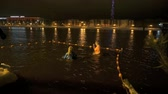 VELIKIY NOVGOROD, RUSSIA - JANUARY 18, 2017: Russian people swimming in cold water in the Volhov river at night winter in Velikiy Novgorod, Russia. Healthy lifestyle. Stock Footage