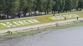 VELIKIY NOVGOROD, RUSSIA - JUNE 22, 2017: Panoramic view of inscription Veliky Novgorod 1158 made from letters of flowers in the background of Volkhov river with walking turists in summer