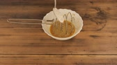 metal powder : White bowl with metal whisk for mixing on a wooden table from the old boards a metal spoon add the flour. In batter of eggs and spices, put in the flour. Cooking batter with eggs in the home kitchen. Stock Footage