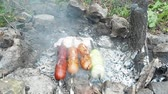 nyárs : Sausages grilling with hot smouldering embers in garden, close up view. Firewoods smoking in fireplace. Fireplace paved with grey stones. Four spits with sausages and onion grilling with hot embers