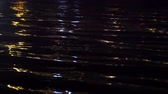 Close-up of reflection of city illumination on sea surface in darkness. Stock Footage