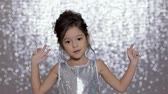 tło : cute happy little girl child in a silver dress dancing on background of silver bokeh. Wideo