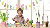 narcis : Happy child wearing bunny ears painting eggs on Easter day. Little boy preparing for the Easter.
