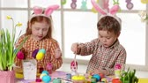 kitchen brushes : Happy children wearing bunny ears painting eggs on Easter day. Little girl and boy preparing for the Easter.