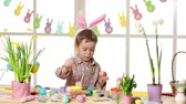 narcissus : Happy child wearing bunny ears painting eggs on Easter day. Little boy preparing for the Easter.