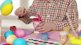 narcis : Happy child wearing bunny ears painting eggs on Easter day. Little boy preparing for the Easter. slow motion