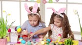 narcis : Happy children wearing bunny ears painting eggs on Easter day. two little girls preparing for the Easter. Dostupné videozáznamy