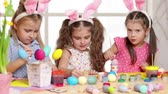 decorative rabbit : Happy children wearing bunny ears painting eggs on Easter day. Little girls preparing for the Easter.