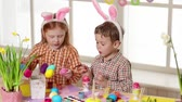 zajączek wielkanocny : Happy children wearing bunny ears painting eggs on Easter day. Little girl and boy preparing for the Easter.